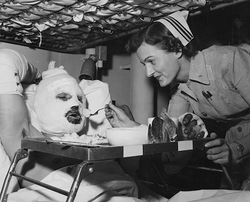 9-Helping-A-Patient-With-His-Meal-Aboard-the-USS-Repose